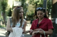 Two happy female friends talking on the street, steadycam shot Stock Footage