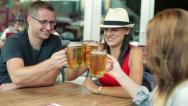 Stock Video Footage of Young happy friends raising a toast with beer in bar, steadicam shot HD