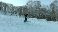 Winter. The boy rides a snowboard from the high snow mountain Stock Footage