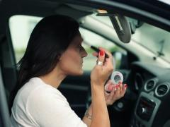Woman applying beauty make-up in the car, steadicam shot NTSC - stock footage