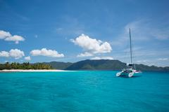 Tropical catamaran sailboat and island in Caribbean Stock Photos