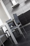 Fragment of modern minimalism style kitchen with dining table Stock Photos