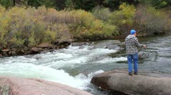 Young man casting and fishing in rushing mountain river Stock Footage