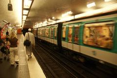 a paris metro train arrives in an underground station - stock photo