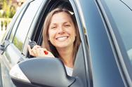Young lady sitting in a car and showing key Stock Photos