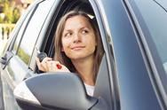 Lady sitting in a car and showing key Stock Photos