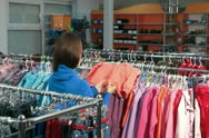 Young Woman Shopping for Children's Clothes Stock Footage