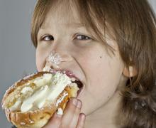 boy enjoying a cream bun with almond paste - stock photo