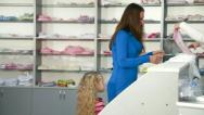 Family Shopping For Childrens Clothes In Clothing Store Stock Footage