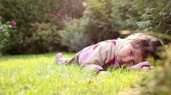 A little girl is rolling in the grass Stock Footage