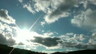 Stock Video Footage of White and gray clouds closing the sun move over a green hill. Time lapse