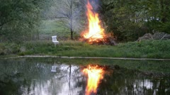 Spring fire in farm near pond and white chair Stock Footage