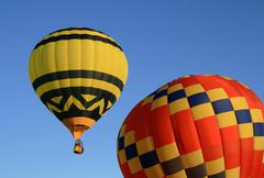 Yellow and red hot air balloons - stock photo