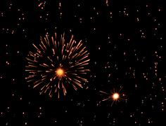 Fireworks exploding in black sky full of sparkles Stock Photos