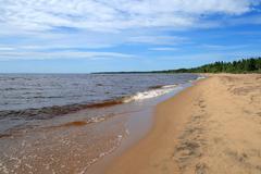 Waves running over sand beach - stock photo