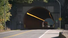 Transport truck wood chip exiting tunnel long shot Stock Footage