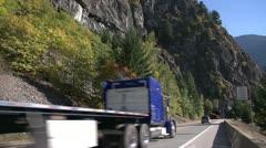 Transport truck flatbed entering tunnel, wide shot Stock Footage