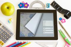 ipad 3 with maps and school accesories - stock photo