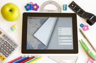 Stock Photo of ipad 3 with maps and school accesories