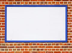 Large white blank billboard sign with a blue wooden frame on a red brick wall. Stock Photos