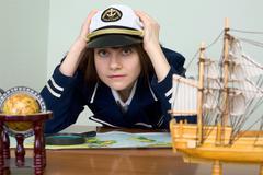 Scared girl in sea uniform at a table Stock Photos