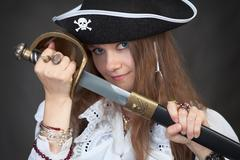 girl in pirate hat with a sabre in hands - stock photo