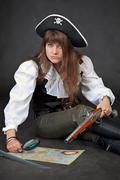 woman in costume of pirate with sea map and magnifier glass - stock photo