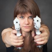 Serious girl aims from two pistols close up Stock Photos