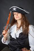Portrait of beautiful girl in pirate hat with pistol in hand Stock Photos