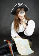 Woman pirate, and map with a magnifying glass on black background Stock Photos