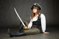 Woman - captain of pirates sitting on black background with a sabre Stock Photos