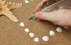 Hand writing with a quill pen on a sandy beach Stock Photos