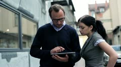Two businesspeople with tablet computer on coffee break, outdoors Stock Footage