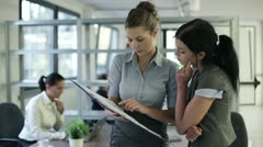 Two smiling businesswomen with documents standing in the office Stock Footage