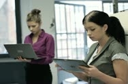 Two businesswoman with tablet and laptop computer in the office hall Stock Footage