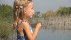 Child Blowing a Dandelion Near a Lake,  Playing Little Girl, Children Stock Footage