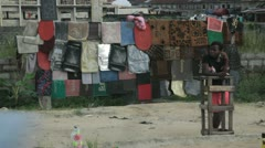 In Africa, Nigeria a streetvendor is making money by selling doormats - stock footage