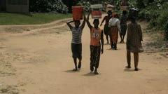 In Africa, Nigeria two boys walk with buckets on their heads Stock Footage