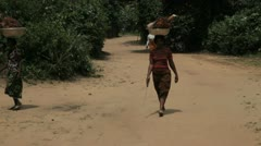 In Africa, Nigeria a woman walks with a baket on her head Stock Footage
