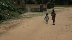 In Africa, Nigeria two children walk by in a small village - stock footage