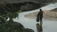 Stock Video Footage of In Africa, Nigeria a fisherman throws his net into the water