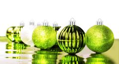 Stock Photo of bright green christmas baubles on white background with space for text