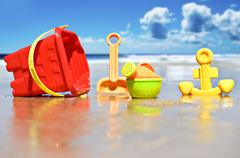 closeup of children's beach toys at the beach  - focus on watering can - stock photo