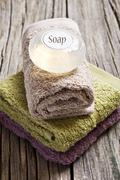 Spa scene with fresh towels and soap on a wooden background Stock Photos