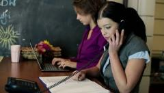 Two young businesswomen talking on landline phone in the office Stock Footage
