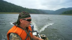 Mature man in the motor boat floating Stock Footage