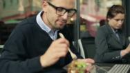 Stock Video Footage of Businessman with laptop eating lunch in cafe, steadicam shot HD