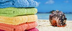 Colorful towels on a white beach with a sea shell Stock Photos
