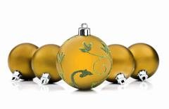 Stock Photo of golden christmas baubles on white background with space for text