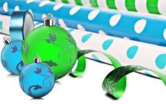 rolls of gift wrapping paper and ribbon with blue and green christmas baubles - stock photo